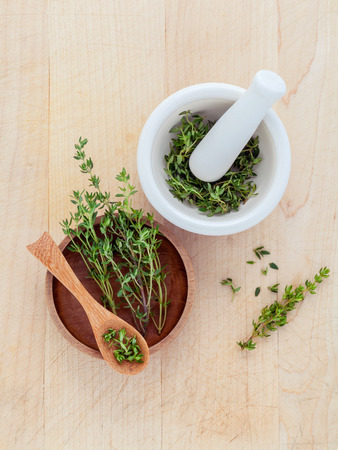 Bunch of fresh organic thyme in white mortar on wooden background Фото со стока - 40833210
