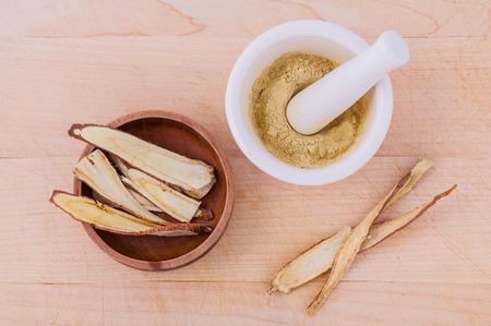medicina: Regaliz medicina herbal incluyendo polvo picado y rodajas de ra�z y el mortero en mesa de madera Foto de archivo