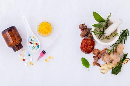 medicamentos: La medicina herbaria VS medicina qu�mica el cuidado saludable alternativa sobre fondo blanco. Foto de archivo