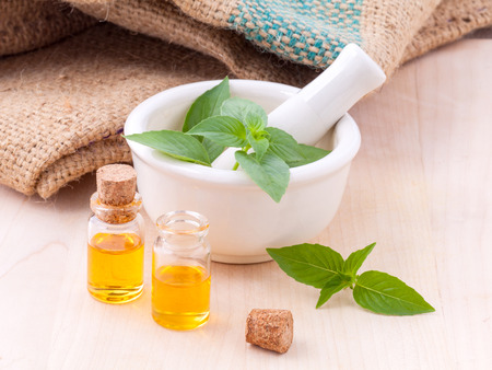 Alternative medicine lemon basil oil natural spas ingredients for aroma aromatherapy with mortar on wooden background. Imagens