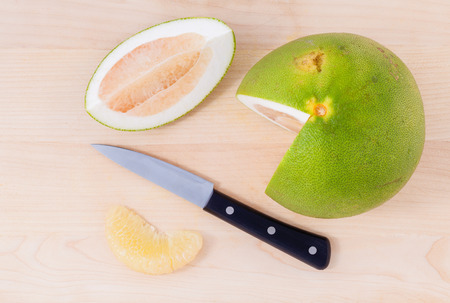 Fresh pomelo cutting and peeled on the wooden background. photo