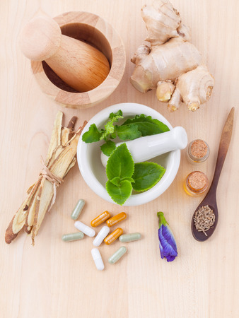 Alternative health care fresh herbal ,dry herbal and herbal capsule with mortar on wooden background.