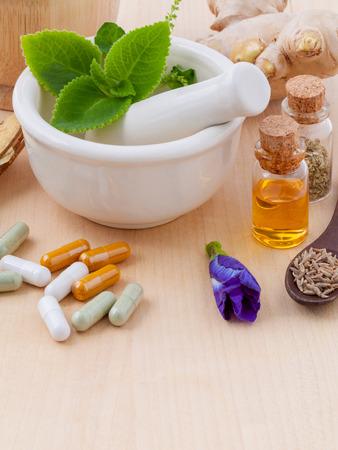Alternative Gesundheits frische Kräuter, trocken und Kräuter-Kapsel mit Mörtel auf hölzernen Hintergrund. Lizenzfreie Bilder
