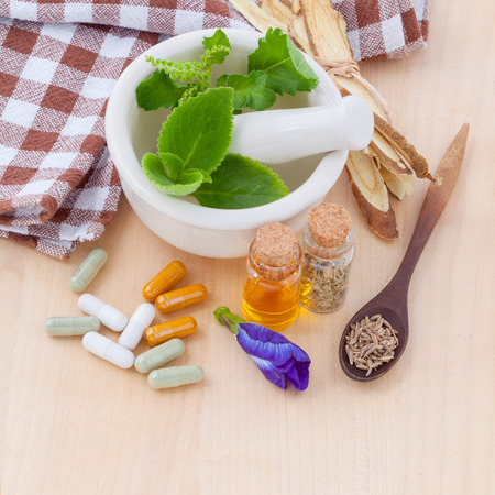 Alternative health care fresh herbal  ,dry and herbal capsule with mortar on wooden background. Standard-Bild