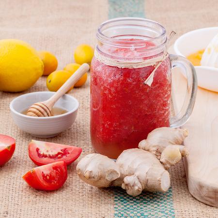 orange juice glass: Freshly tomato juice with tomato slice, ginger ,oranges , honey ,kiwi ,mint and orange juice set up on wooden table .