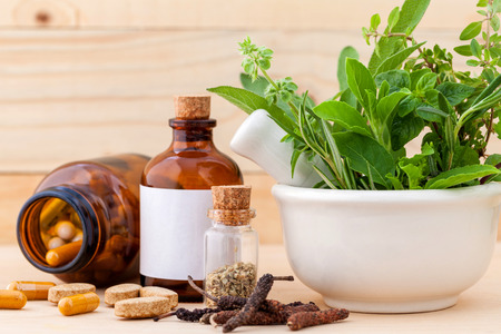nature cure: Alternative health care fresh herbal  ,dry and herbal capsule with mortar on wooden background. Stock Photo