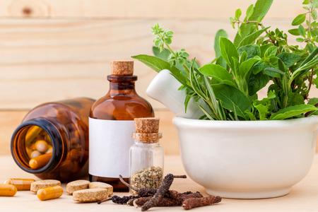 homeopathy: Cuidado de la salud a base de hierbas frescas Alternativa, cápsula seca y hierbas con mortero sobre fondo de madera.