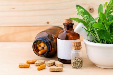 건강: 대체 의료 신선한 허브, 나무 배경에 박격포와 건조 허브 캡슐. 스톡 콘텐츠