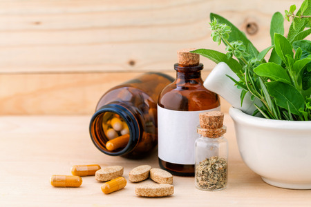 Alternative health care fresh herbal  ,dry and herbal capsule with mortar on wooden background. Banco de Imagens