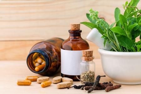 代替医療新鮮なハーブ、乾燥したハーブのカプセル木製の背景にモルタル。 写真素材