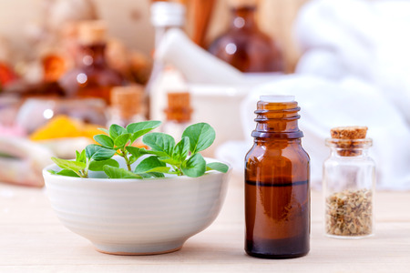 Natural Spa Ingredients essential oil with oregano leaves for aromatherapy setup on spa ingredients background. Stock Photo