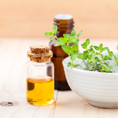 Bottle of essential oil and lemon thyme  leaf  on wooden background. Imagens