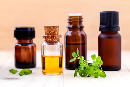 tomillo: Botella de aceite esencial de lim�n y tomillo hojas sobre fondo de madera.