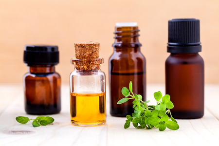 Bottle of essential oil and lemon thyme  leaf  on wooden background. Archivio Fotografico