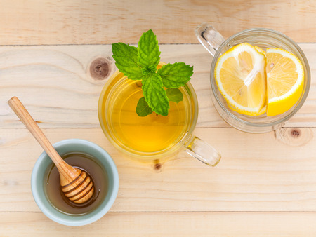 lemon water: Cup of herbal tea with fresh green mint ,honey and lemon on wooden background. Stock Photo