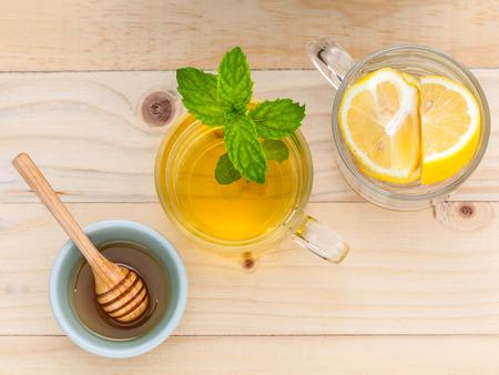 lemon: Taza de t� de hierbas con fresca verde menta, miel y lim�n sobre fondo de madera.