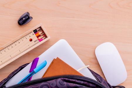 fournitures scolaires: Sac à dos avec des fournitures scolaires pour ordinateur portable, livre stationnaire, souris, un crayon, règle, crayon de couleur sur la table en bois. Banque d'images