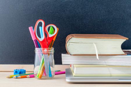 material escolar: Volver al concepto de escuela con útiles escolares portátil, libro, pluma, ratón y lápiz de color en la mesa de madera.