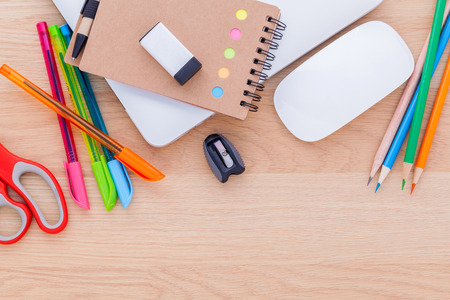 Back to school concept with school supplies laptop ,notebook, pen,mouse,and colored pencil on wooden table . Stock Photo