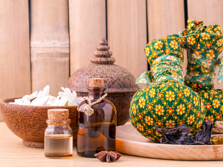 thai spa: Natural Spa Ingredients herbal compress ball and essential Oil for alternative medicine and relaxation Thai Spa theme with bamboo background. Stock Photo