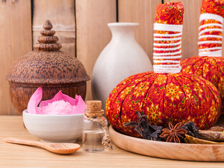 thailand bamboo: Natural Spa Ingredients herbal compress ball and essential Oil for alternative medicine and relaxation Thai Spa theme with bamboo background. Stock Photo