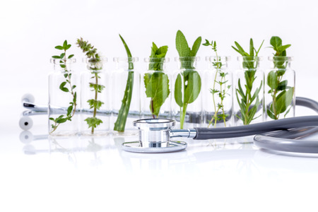 Bottle of essential oil with herb holy basil leaf, rosemary,oregano, sage,basil and mint with stethoscope on white background. Stock Photo
