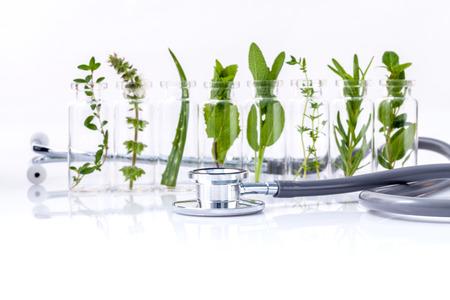 Flesje etherische olie met kruid heilige basilicum blad, rozemarijn, oregano, salie, basilicum en munt met een stethoscoop op een witte achtergrond.