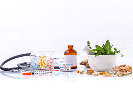 Kruidengeneeskunde VS Chemical geneeskunde het alternatief gezonde zorg met een stethoscoop isoleren op een witte achtergrond.
