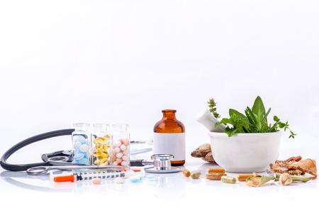 acupuntura china: La medicina herbaria VS medicina qu�mica el cuidado saludable alternativa con el estetoscopio aislado en el fondo blanco.