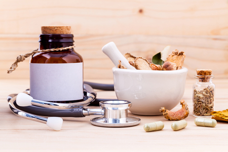 Capsule of herbal medicine alternative healthy care with stethoscope on wooden background.