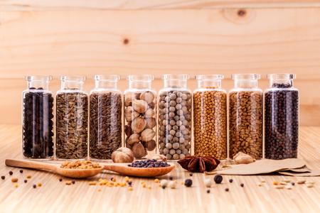 epices: Assortiment de bouteilles d'épices condiment poivre noir, poivre blanc, la moutarde noire, la moutarde blanche, le fenugrec, le cumin et les graines de fenouil sur fond de bois. Banque d'images