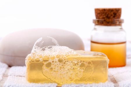 champu: Herbal barra de jabón balneario en la toalla de baño blanco con miel aislado en el fondo blanco.