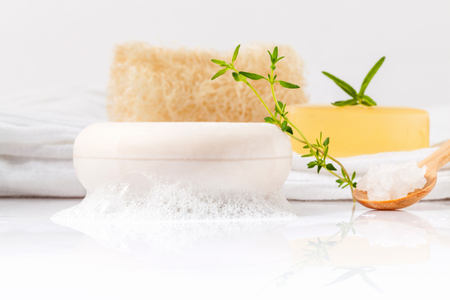 water thyme: Herbal spa soap bar on white bath towel with thyme,rosemary and luffa isolated on white background.
