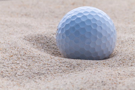 Close-up golfbal in het zand bunker ondiepe scherptediepte. Stockfoto