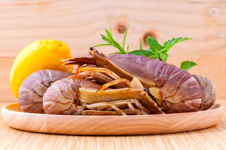 flathead: Raw Flathead lobster, Lobster Moreton Bay bug, Oriental flathead lobster on wooden background.