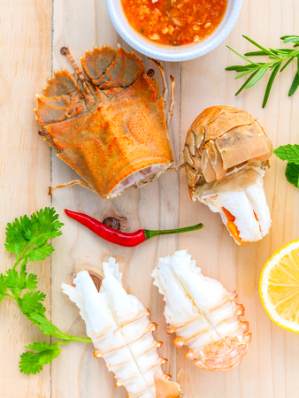 Boiled Flathead lobster, Lobster Moreton Bay bug, Oriental flathead lobster with herbs and spices  sauce on wooden background.