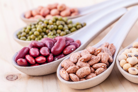 Sortiment von Bohnen und Linsen in Holzlöffel auf hölzernen Hintergrund. Mungbohne, Erdnuss, Soja, rote Kidney-Bohnen, schwarze Bohnen, rote Bohnen und braunen Bohnen Pinto.