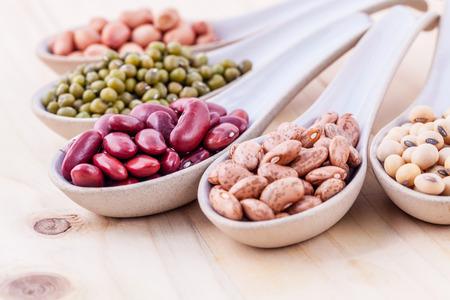 나무 배경에 나무로되는 숟가락에 콩, 렌즈 콩의 구색. 녹두 콩, 땅콩, 콩, 붉은 강낭콩, 검은 콩, 팥, 갈색 핀 토 콩.