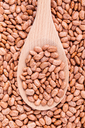Brown pinto beans in wooden spoon and brown pinto beans  background.