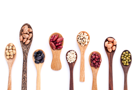 Sortiment von Bohnen und Linsen in Holzlöffel auf weißem Hintergrund isolieren. Mungbohne, Erdnuss, Soja, rote Kidney-Bohnen, schwarze Bohnen, rote Bohnen und braunen Bohnen Pinto.