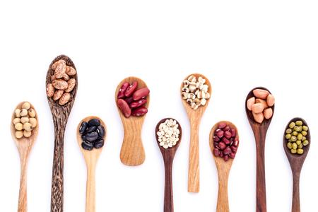 ejotes: Surtido de frijoles y lentejas en cuchara de madera aislado en el fondo blanco. frijol mungo, maní, soja, frijol rojo, frijol negro, frijol rojo y judías pintas marrones.