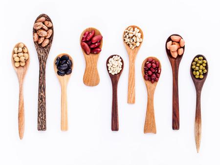 콩 및 나무 숟가락에 렌즈 콩의 구색 흰색 배경에 격리합니다. 녹두, 땅콩, 콩, 붉은 강낭콩, 검은 콩, 팥, 갈색 핀토 콩.