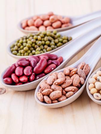 콩 및 나무 배경에 나무로되는 숟가락에 렌즈 콩의 구색. 녹두, 땅콩, 콩, 붉은 강낭콩, 검은 콩, 팥, 갈색 핀토 콩.