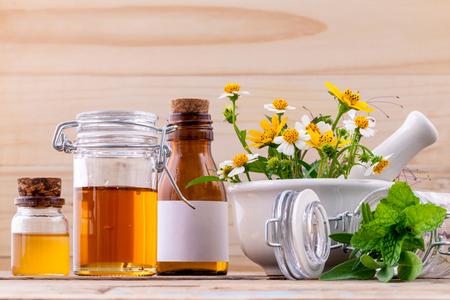 대체 의학 신선한 허브, 꿀, 나무 배경에 박격포와 야생 꽃.