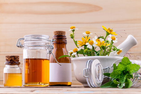 Alternative health care fresh herbal ,honey and wild flower with mortar on wooden background. Zdjęcie Seryjne