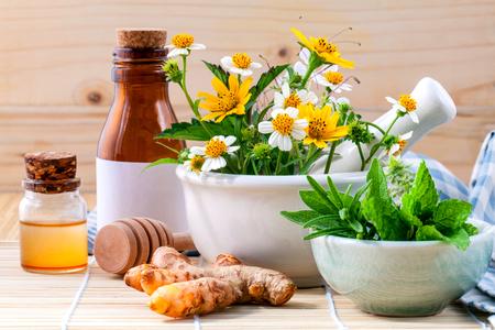 Alternatieve gezondheidszorg verse kruiden, honing en wilde bloemen met mortel op houten achtergrond.