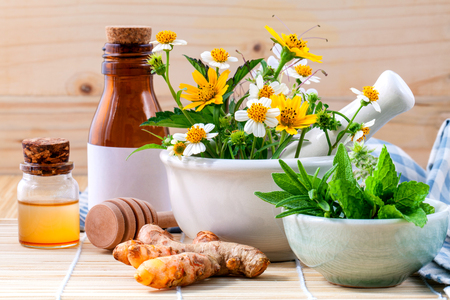 Alternative health care fresh herbal ,honey and wild flower with mortar on wooden background. Stock Photo