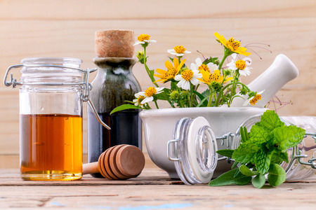 Alternative health care fresh herbal ,honey and wild flower with mortar on wooden background. Imagens