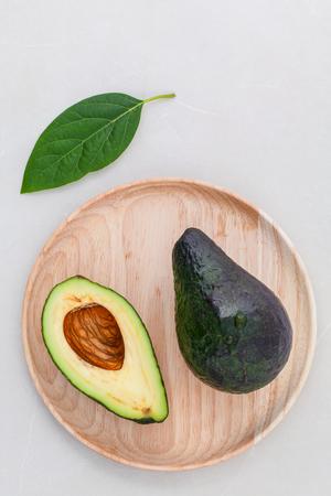 alternative health: Alternative health care fresh  avocado and leaves on marble background. Stock Photo