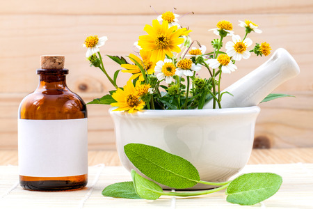 alternative health: Alternative health care fresh herbal ,oil and wild flower with mortar on wooden background.